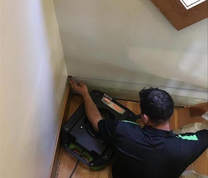A SERVPRO of Missoula technician removes wet material in a stairwell.