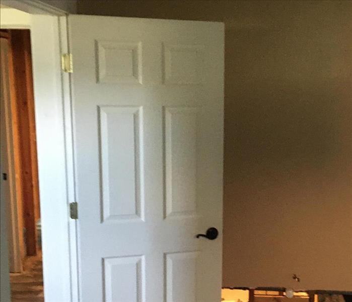 A door is reinstalled after mold mitigation has been completed on it.