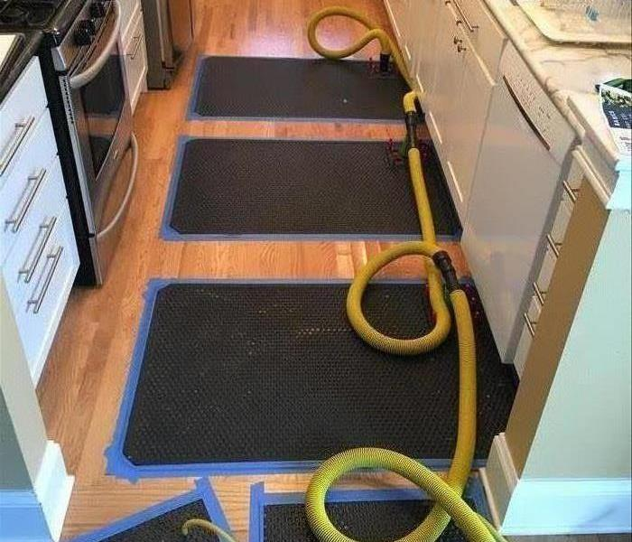 Water extraction mats placed over a hardwood, kitchen floor.