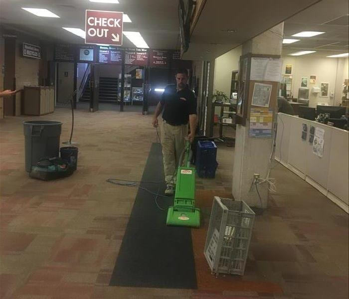 A technician vacuuming a carpet after a counter was removed.