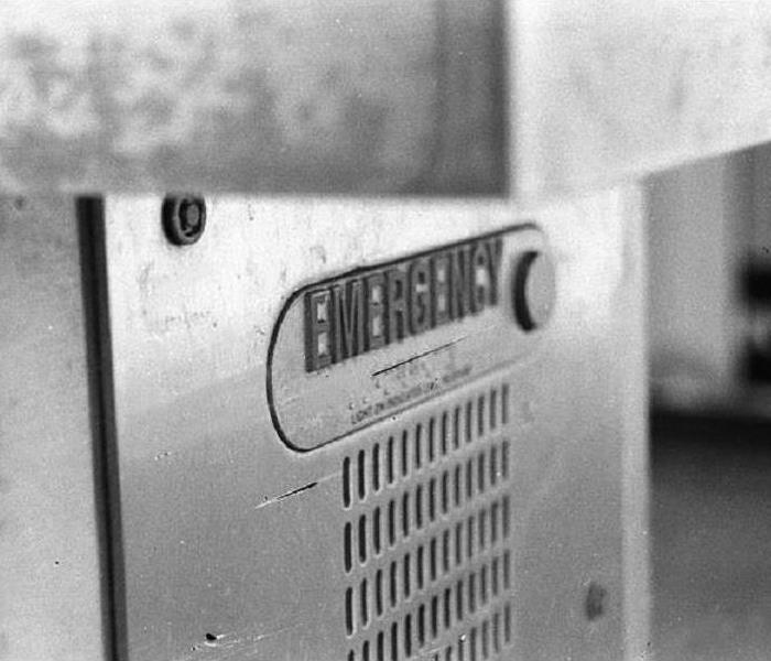 A black and white photo of an emergency call box on a college campus.