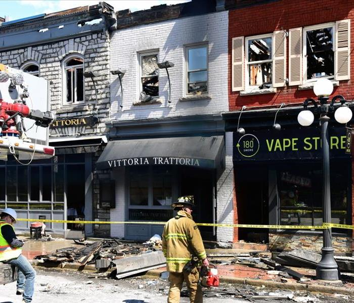 A fire fighter stands outside a burned-out restaurant façade.