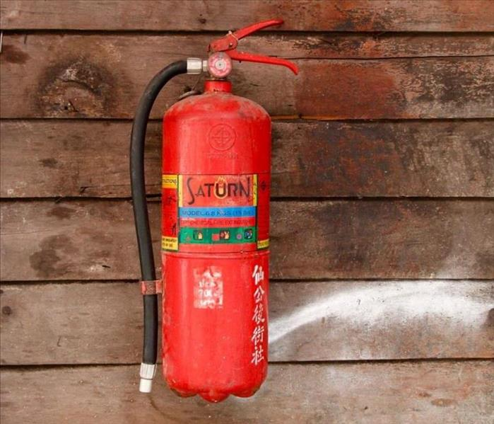 A fire extinguisher hangs on a wall.