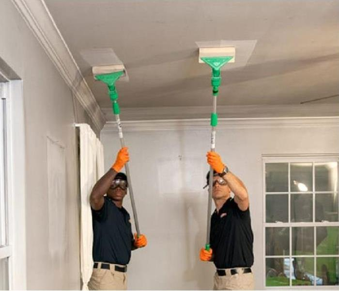 Two SERVPRO technicians cleaning smoke damage off a ceiling.