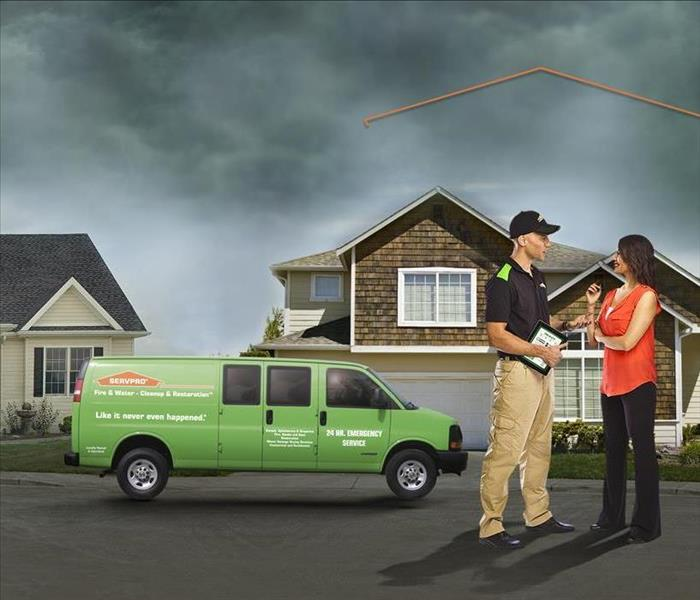 SERVPRO technician talking to a customer outside a house.