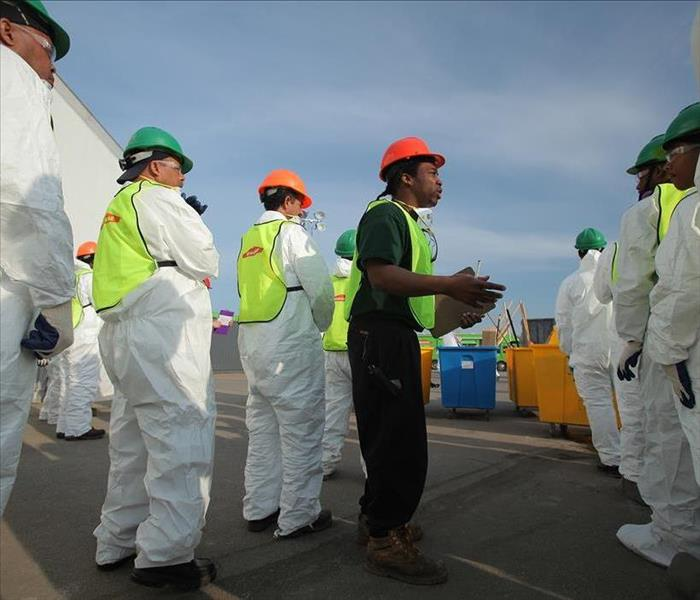 A project manager briefs SERVPRO technicians in full PPE on work to be done.